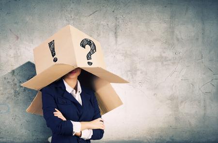Zakenvrouw dragen kartonnen doos met markeringen op het hoofd Stockfoto