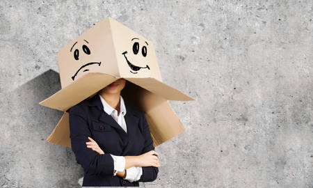 Businesswoman wearing carton box with drawn smiley on head photo