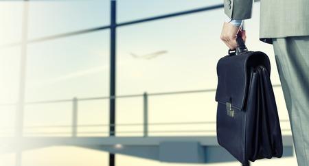 コンピューターの背面のスーツケースと空港で実業家の手に