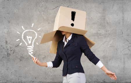acknowledge: Businesswoman using mobile phone wearing carton box on head