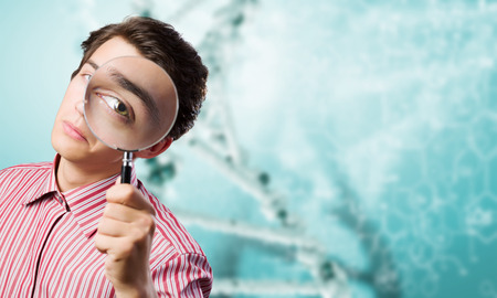 Young man in casual looking in magnifier Stock Photo