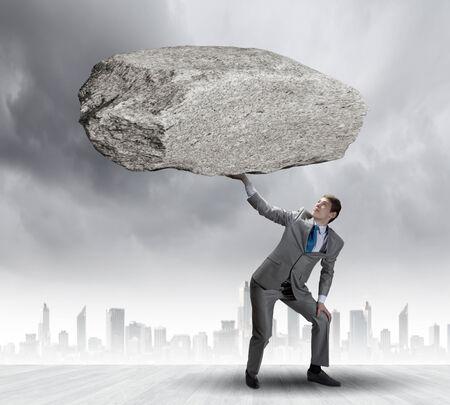 oppressed: Powerful businessman holding huge stone above head Stock Photo