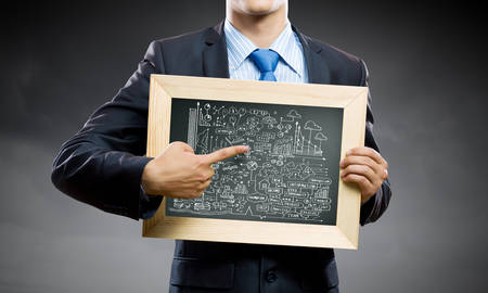 Close up of businessman holding frame with business sketch photo