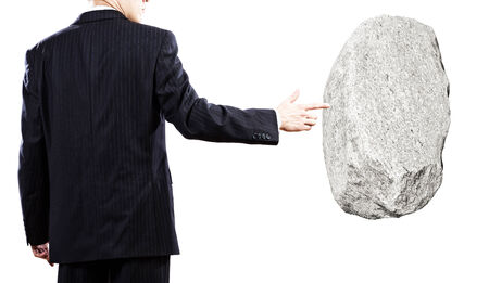 burdensome: Businessman in suit pointing at huge stone