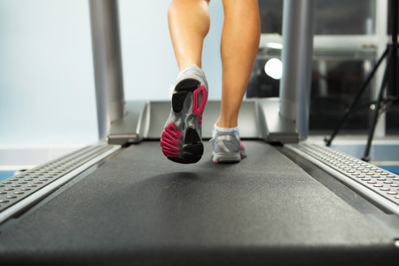 Image of female foot running on treadmill photo