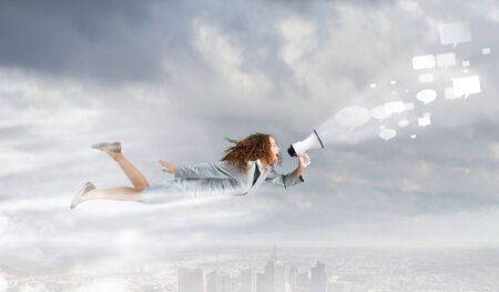 Young businesswoman with megaphone flying high in sky photo