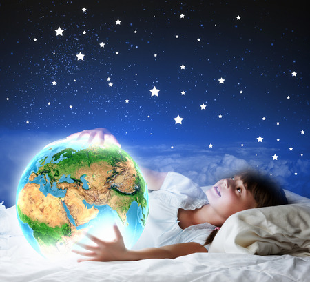 Cute girl sleeping in bed and looking at Earth planet photo