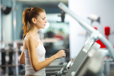 Image of fitness girl running on treadmill photo