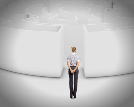 hard way: Thoughtful businesswoman standing near the enter of labyrinth Stock Photo