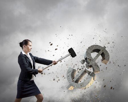 Young businesswoman crashing with hammer stone dollar symbol photo