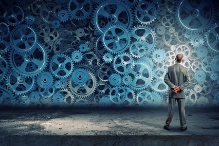 business collaboration: Back view of businessman looking at mechanism of cogwheels