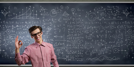 Young funny man in glasses against chalkboard with sketches photo
