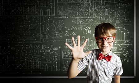 Genius boy in red glasses near blackboard with formulas Stock Photo - 26045310