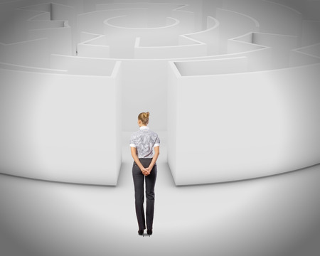 Thoughtful businesswoman standing near the enter of labyrinth Stock Photo