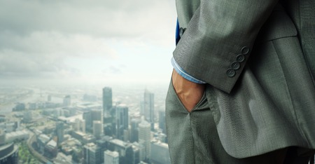 businessman standing: Close up of businessman standing on top viewing at city