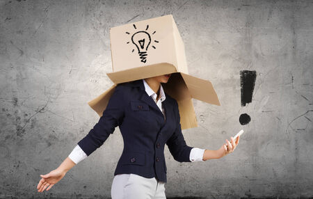 unknown gender: Businesswoman using mobile phone wearing carton box on head