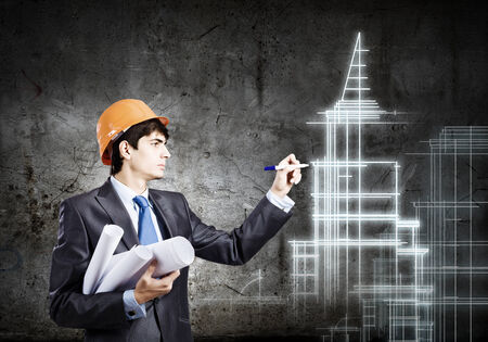 project: Young man engineer in helmet drawing construction project Stock Photo