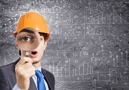 Young man engineer with magnifier against sketch background Reklamní fotografie