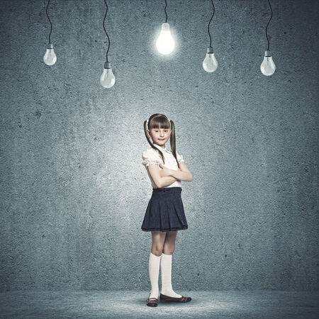 Little cute girl and electric bulbs hanging above photo
