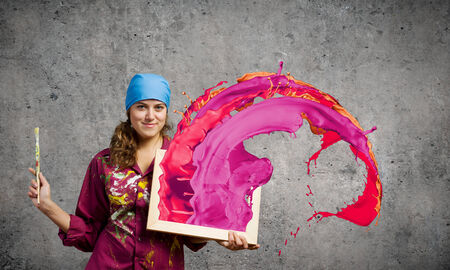 Young woman painter with palette and brush photo