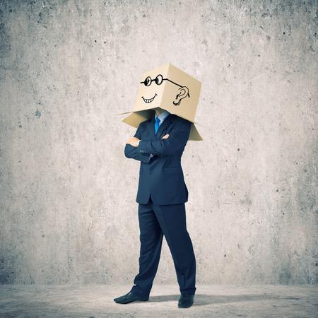 cowardice: Businessman wearing carton box with smileys on head