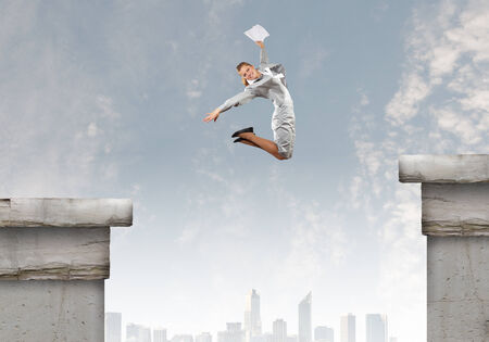 Young businesswoman jumping over gap  Risk concept photo