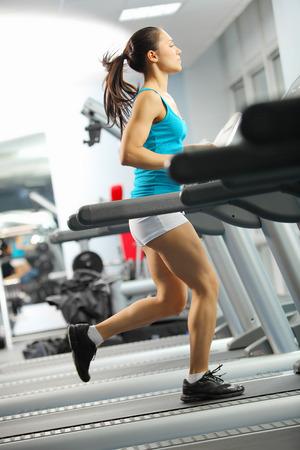Image of fitness girl running on treadmill photo