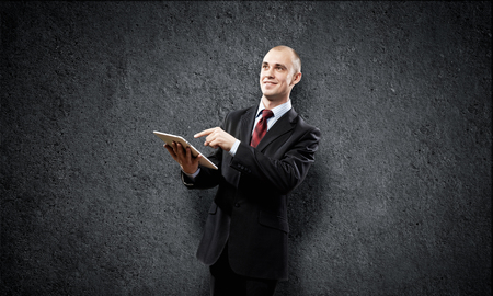 Young businessman against grey background using tablet pc photo