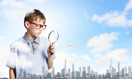 schoolkid search: Cute school boy examining objects with magnifying glass