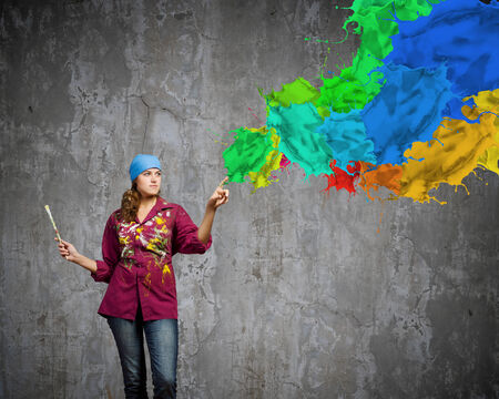 Young woman painter coloring wall with brush photo