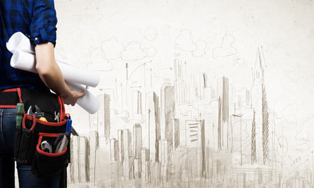 Close up of woman mechanic with project in hand against city background photo