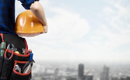 Close-up van de vrouw monteur met gele helm in de hand tegen de stad achtergrond