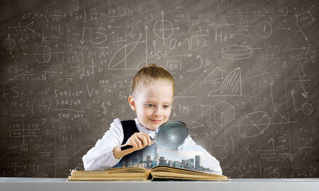 schoolkid search: Schoolgirl examining opened book with magnifying glass Stock Photo