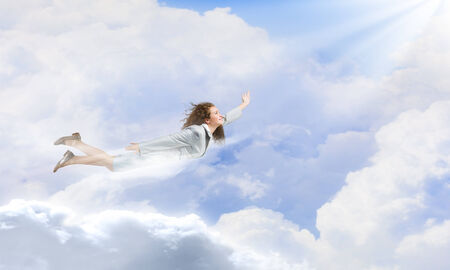 Young happy businesswoman flying high in sky photo