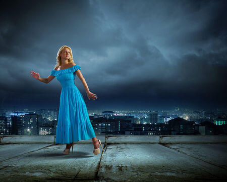Anxious young woman in blue dress looking back worried photo