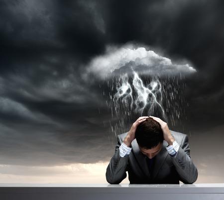 Depressive junge Geschäftsmann sitzt unter regen nass