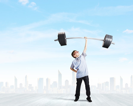 Cute boy of school age lifting barbell above head