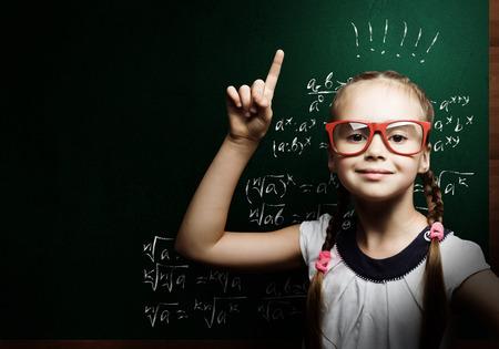 Genie meisje in rode glazen dichtbij bord met formules