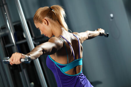 raise your hand: Image of fitness girl in gym exercising with dumbbells Stock Photo