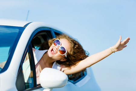 woman driving car: Young pretty woman driving car and leaning out of car window Stock Photo