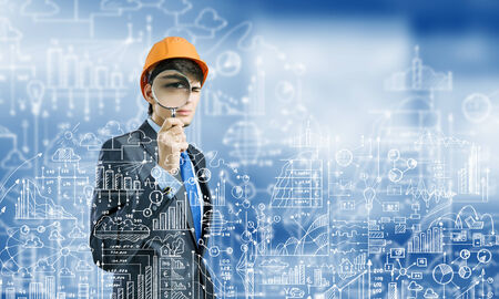 Young man engineer with magnifier against sketch background photo
