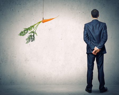 attracts: Funny image of businessman chased with carrot