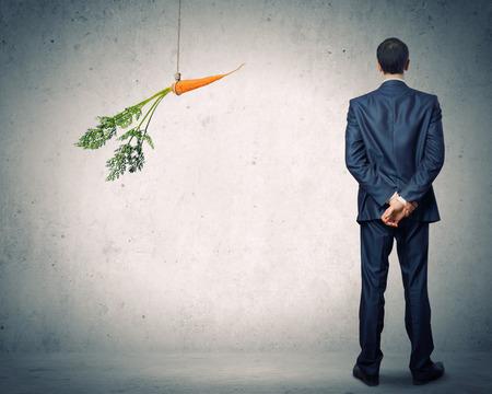 Grappig beeld van zakenman achtervolgd met wortel