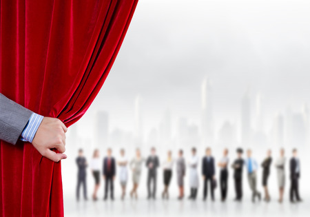 Hand of businessman opening red velvet curtain photo