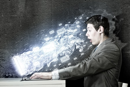 censor: Young man sitting at table and using laptop Stock Photo