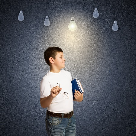 School boy and electric bulbs hanging above photo