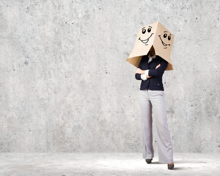 Confident businesswoman wearing carton box on head photo