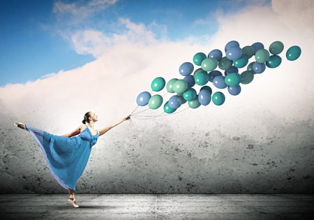 Young woman in dress and ballerinas dancing with colorful balloons