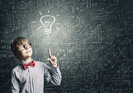 Genie jongen in het rood glazen dichtbij bord met formules Stockfoto