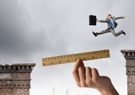Young businessman jumping over gap  Risk concept Stock Photo